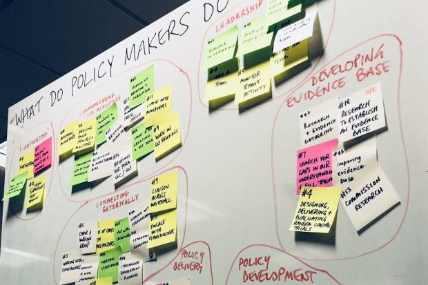 Photograph of a whiteboard full of coloured sticky notes, clustered into smaller groups with descriptions under the headline 'What do policymakers do?'; the cluster descriptions read: Policy delivery, connecting externally, policy development, developing evidence base, leadership, communicating with ministers