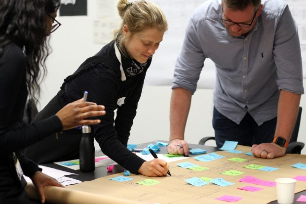 Three people in a workshop creating a user journey map on a brown paper roll with coloured sticky notes