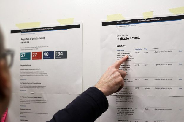 A person pointing at a printed list of services designed as digital by default