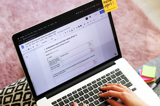 A person writing a COVID-19 services peer review discussion report on a laptop computer, on the screen a headline reads: 1. Understand users and their needs (Point 1)