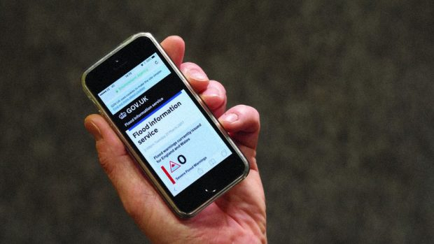 A smartphone in person's hand, displaying the flood information service page on GOV.UK, indicating the current flood warnings in England and Wales.