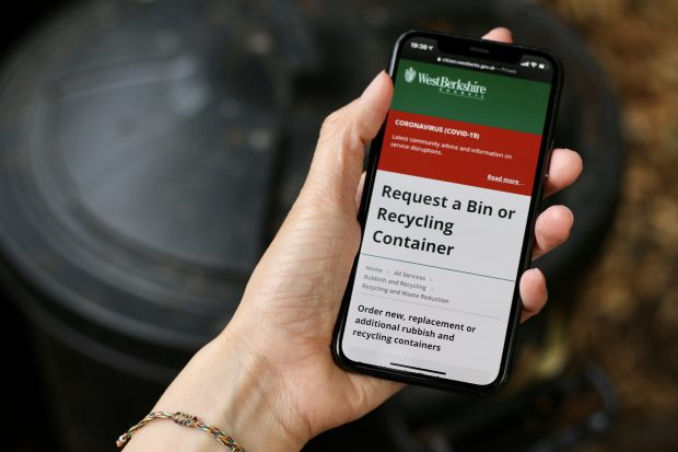 A woman's hand holding a smartphone with the digital service interface of West Berkshire Council's Request a bin or recycling container service