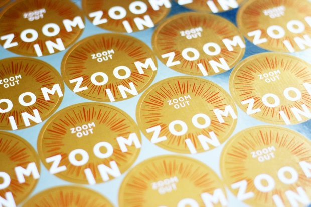 A sheet of yellow-golden stickers saying zoom out, zoom in made for participants of service design training