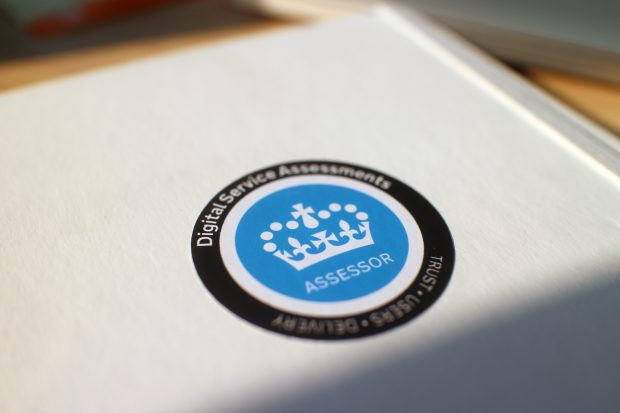 A sticker with the Crown symbol saying 'ASSESSOR – Digital Service Assessments' on a white notebook
