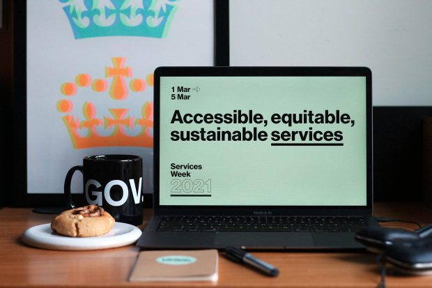 A computer on a desk showing a Services Week 2021 screen saying: Accessible, equitable, sustainable services