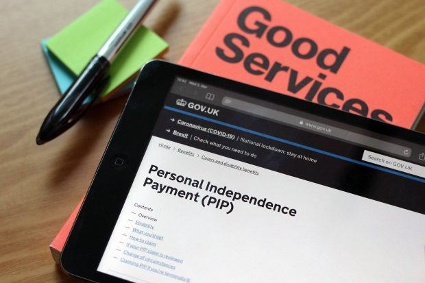 A tablet showing the Personal Independence Payment (PIP) guidance on GOV.UK next to a book saying Good Services