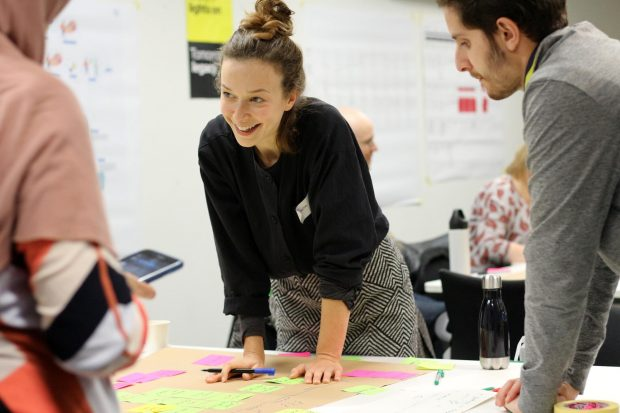 A group of people standing over a service blueprint draft, the central person, a young woman, holding a pen and rearranging stickie notes