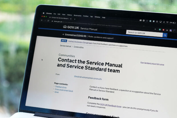 A laptop screen showing a web page on contacting the Service Manual and Service Standard team