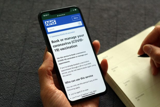 The NHS Book your coronavirus vaccination online service shown on a mobile phone held by a person who's taking a note in their diary