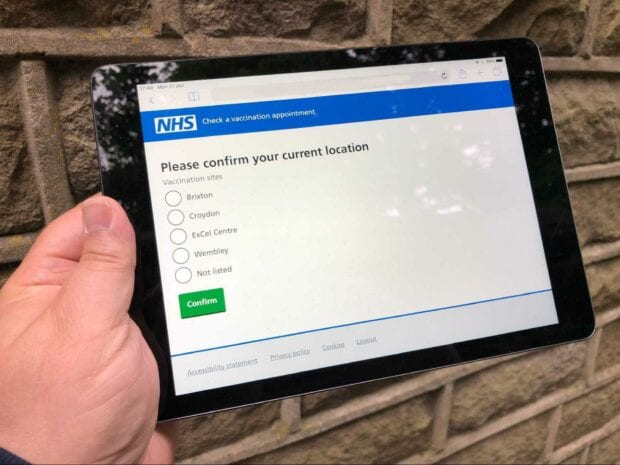 A person's hand holding a tablet computer showing the web application for checking a vaccination appointment used by NHS staff in vaccination centres
