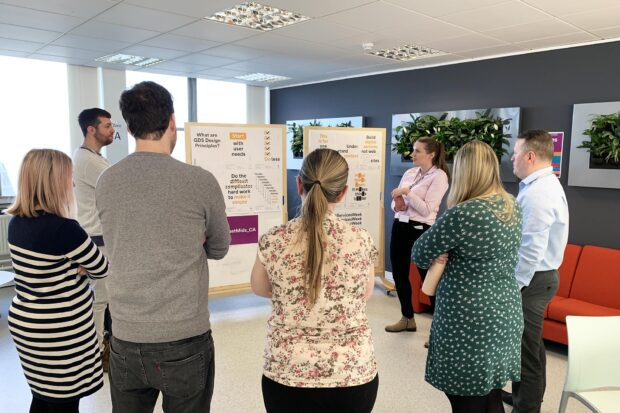 Members of the WMCA digital team standing in a circle discussing the GDS design principles that are pinned to a whiteboard they are looking at